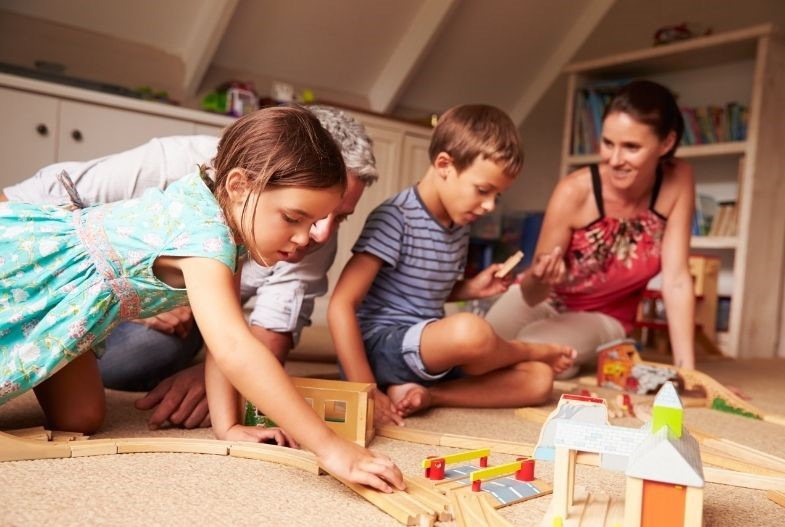 Parents playing on the floor building a wooden train track with their children