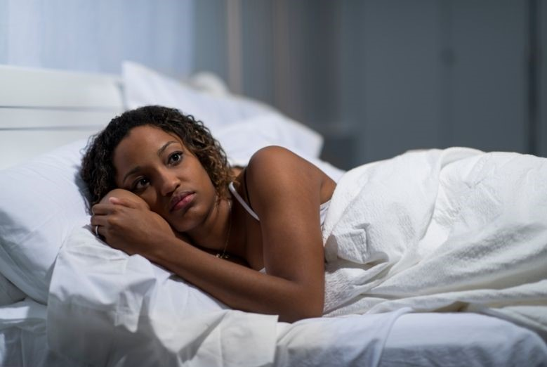 Lady lays wide awake in bed