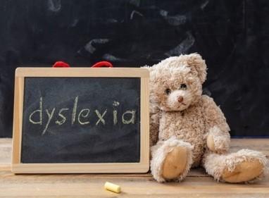 Teddy Bear sitting beside chalkboard sign with Dyslexia written on it