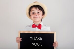 """Child holding chalkboard that says """"thank you"""""""