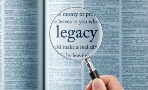 """magnifying glass reading the word """"legacy"""" in a dictionary"""